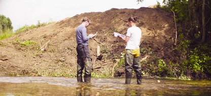 Two Authors in waders recording information about catches